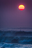 Smoke in the air colors the sun on a summer evening; Seaside, Oregon, United States of America
