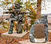 A memorial plaque with inukshuk among some trees in autumn; Edmonton, Alberta, Canada