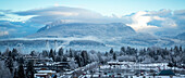 View of clouds hovering over mountains and snow covering the neighbourhood in the foreground; Surrey, British Columbia, Canada