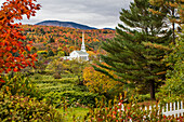 Stowe Church surrounded by lush and autumn coloured foliage with forest on the hillside; Stowe, Vermont, United States of America