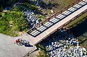 View from directly above a cyclist in a red shirt going down a path and onto a bridge over a creek; Calgary, Alberta, Canada