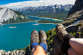 Close-up of a couple's hiking boots over a cliff overlooking a colourful alpine lake and mountain range in the distance; Kananaskis Country, Alberta, Canada