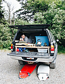 Woman lying in bed in trunk of SUV during surfing road trip, La Push, Washington State, USA