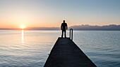 Lonely man standing on pier by Geneva Lake, at sunrise in summer, Gland, Vaud, Switzerland