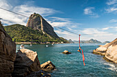 Woman doing aerial acrobatics hanging from highline next to Sugarloaf Mountain in Rio de Janeiro, Brazil