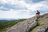 Female backpacker sitting and looking at view from summit of Cadillac Mountain in Acadia National Park, Bar Harbor, Maine, USA