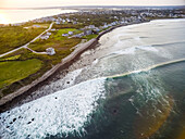 An aerial drone photograph of large hurricane swell sweeping up the coast in long lines during sunset at Point Judith, Rhode Island, from Hurricane Jose