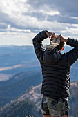 Woman preparing for outdoor adventure by securing ponytail while looking at mountain view, Jackson Hole, Wyoming, USA