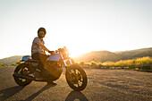 Side view of man sitting on motorcycle at sunset, Emigration Canyon, Utah, USA