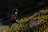 Woman trail running up hill in meadow with wildflowers, Alta, Utah, USA