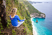 Blonde woman meditating on edge of coastline cliff, Bali, Indonesia