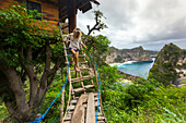 Woman walking down steps outside hut on coast with cliffs, Nusa Penida, Bali, Indonesia