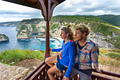 Couple on vacations looking at view of ocean from oceanside hut, Nusa Penida, Bali, Indonesia