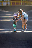 Mother and son with push scooter in skate park, Canggu, Bali, Indonesia