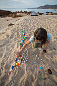 An adult woman making an artful design on the beach with plastic caps that she collected. Baja California del Sur, Mexico.