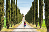 Castiglion d'Orcia, Orcia valley, Siena, Tuscany, Italy, A young woman in casual clothes is walking along a country road
