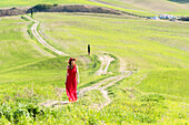 San Quirico d'Orcia, Orcia valley, Siena, Tuscany, Italy, A young woman in red dress walking along a country path near the cypresses of val d'orcia