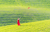 San Quirico d'Orcia, Orcia valley, Siena, Tuscany, Italy, A young woman in red dress is throwing her hat in a wheat field