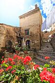The sun illuminates a flowered balcony in the historic center of Santo Stefano di Sessanio, Abruzzo, Italy