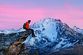 An hiker on a rock admiring Piazzi peak at sunset, Valdidentro, Valtellina, Lombardy, Italy