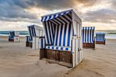 Kampen, Sylt island, North Frisia, Schleswig-Holstein, Germany, Strandkorbs on the beach at sunset