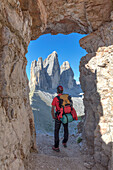 Hiker looking the Tre Cime di Lavaredo / Drei Zinnen through a window in the rock at the foot of the mount Paterno / Paternkofel, Sexten Dolomites, South Tyrol, Bolzano, Italy
