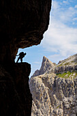 Italy, South Tyrol, Sexten, Hochpustertal, Bolzano, Hiker in silhouette on the Alpinisteig or Strada degli Alpini via ferrata, Sexten Dolomites