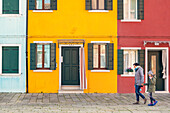 tourists walk in front of the colorful houses of Burano, Venice, Veneto, Italy