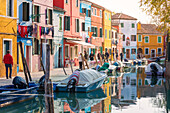 a lively street of burano, the colorful houses overlook the canal and people walk, Burano island, Venice, Veneto, Italy