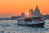 Venetian Vaporetto on the Grand Canal at sunset with Basilica of Saint Mary of Health, in background, Punta della Dogana, Venice, Veneto, Italy