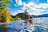 Avelengo,Bolzano province,Trentino Alto Adige,Italy Girl relaxes in the pool admiring the landscape