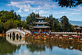 Tourists over arched bridge at Black Dragon Pool, Lijiang, Yunnan Province, China, Asia, Asian, East Asia, Far East