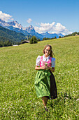 A girl in typical dress into the alpine landscape of GErold, Garmisch Partenkirchen Land, Bayern, Germany