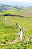 San Quirico d'Orcia, Orcia valley, Siena, Tuscany, Italy, A young woman in casual clothes is walking along a country road