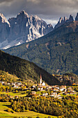 an autumnal view of Teis, a small village in Villnössertal with the Geisler Group in the background, Bolzano province, South Tyrol, Trentino Alto Adige, Italy
