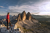 Sesto / Sexten, province of Bolzano, Dolomites, South Tyrol, Italy, A mountaineer admires the sunset at the Three Peaks of Lavaredo