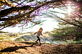 Caucasian girl running under tree branches