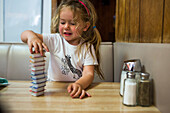 Smiling Caucasian girl stacking jelly containers in restaurant booth