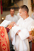Priest blessing baby boy in church