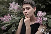 Curious Caucasian woman near flowering tree with finger on lip