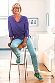 Smiling Caucasian woman sitting on stool