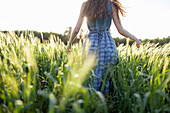 Caucasian woman walking in field of tall grass