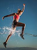 Water splashing on Caucasian woman running in sky
