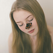 Butterfly on nose of Caucasian teenage girl