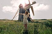 Caucasian woman balancing in grass near windmill