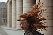Wind blowing hair of Caucasian woman near pillars