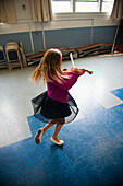 Caucasian girl practicing violin and dancing