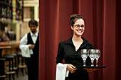 Smiling Hispanic waitress carrying tray of wine glasses