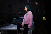 Caucasian woman sitting on hood of car at night