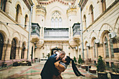 Caucasian couple kissing in courtyard